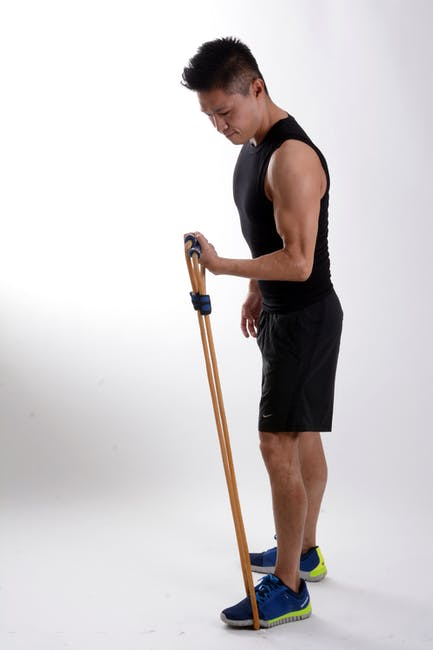 Man in Black Tank Top Holding Brown Stretching Rope