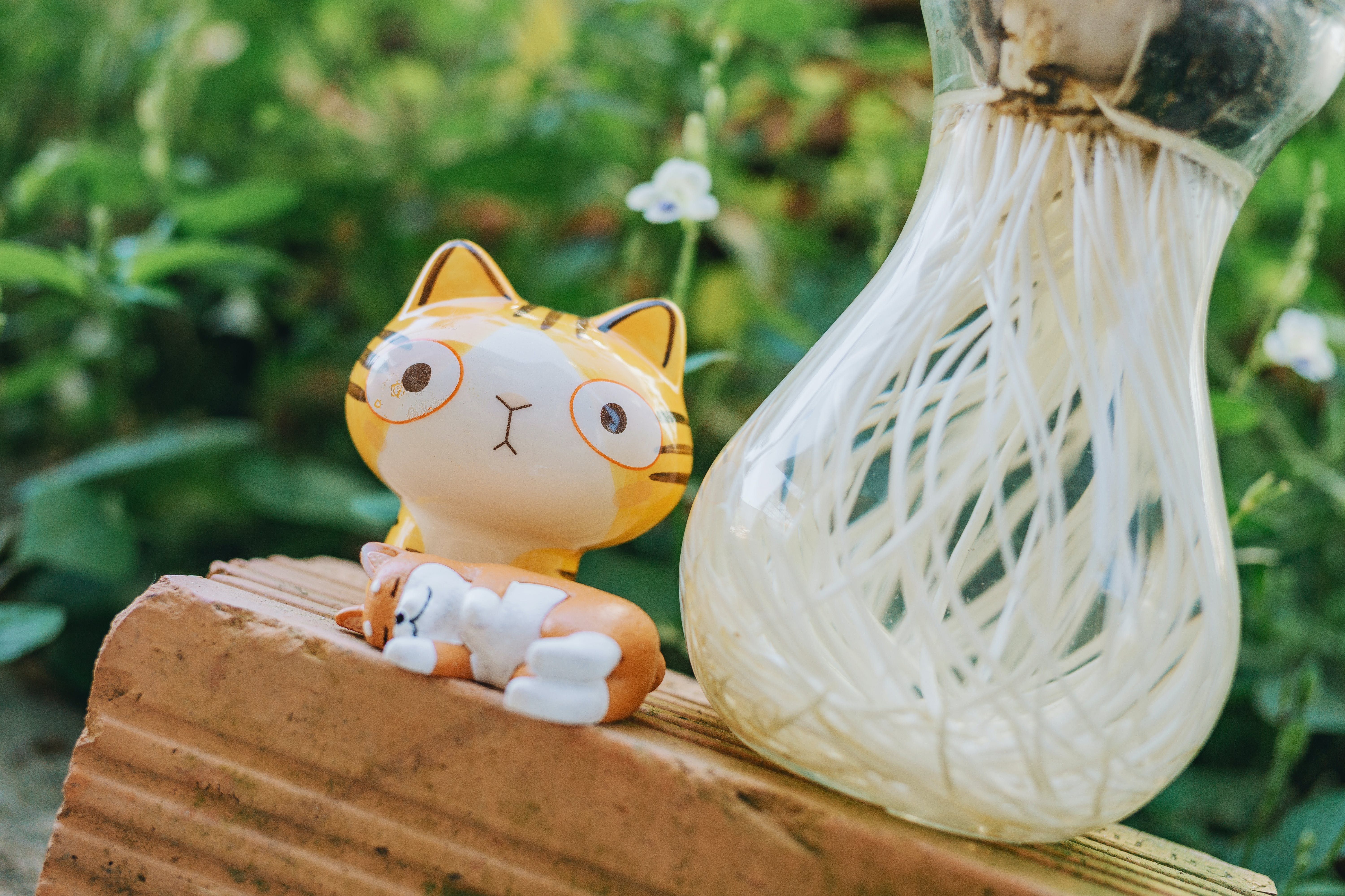 Yellow Cat Figurine Beside Clear Glass Vase