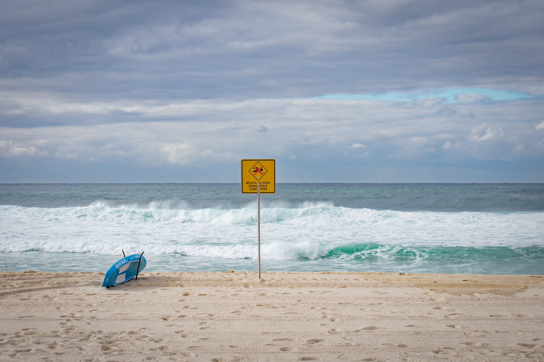 Blue Surfboard at Shoreline Near Signage