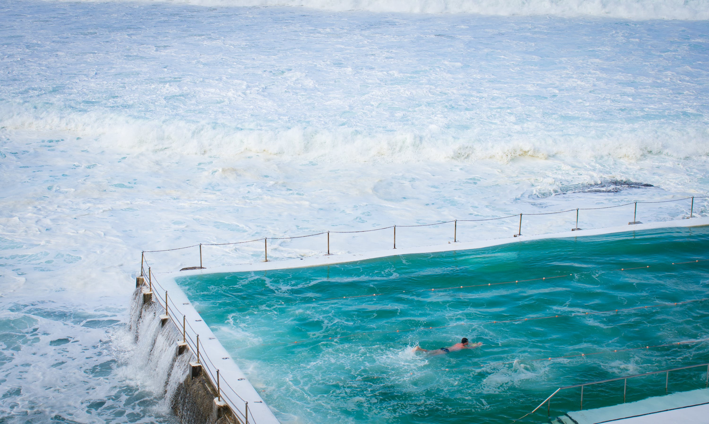 Person Swimming on Pool Beside Ocean