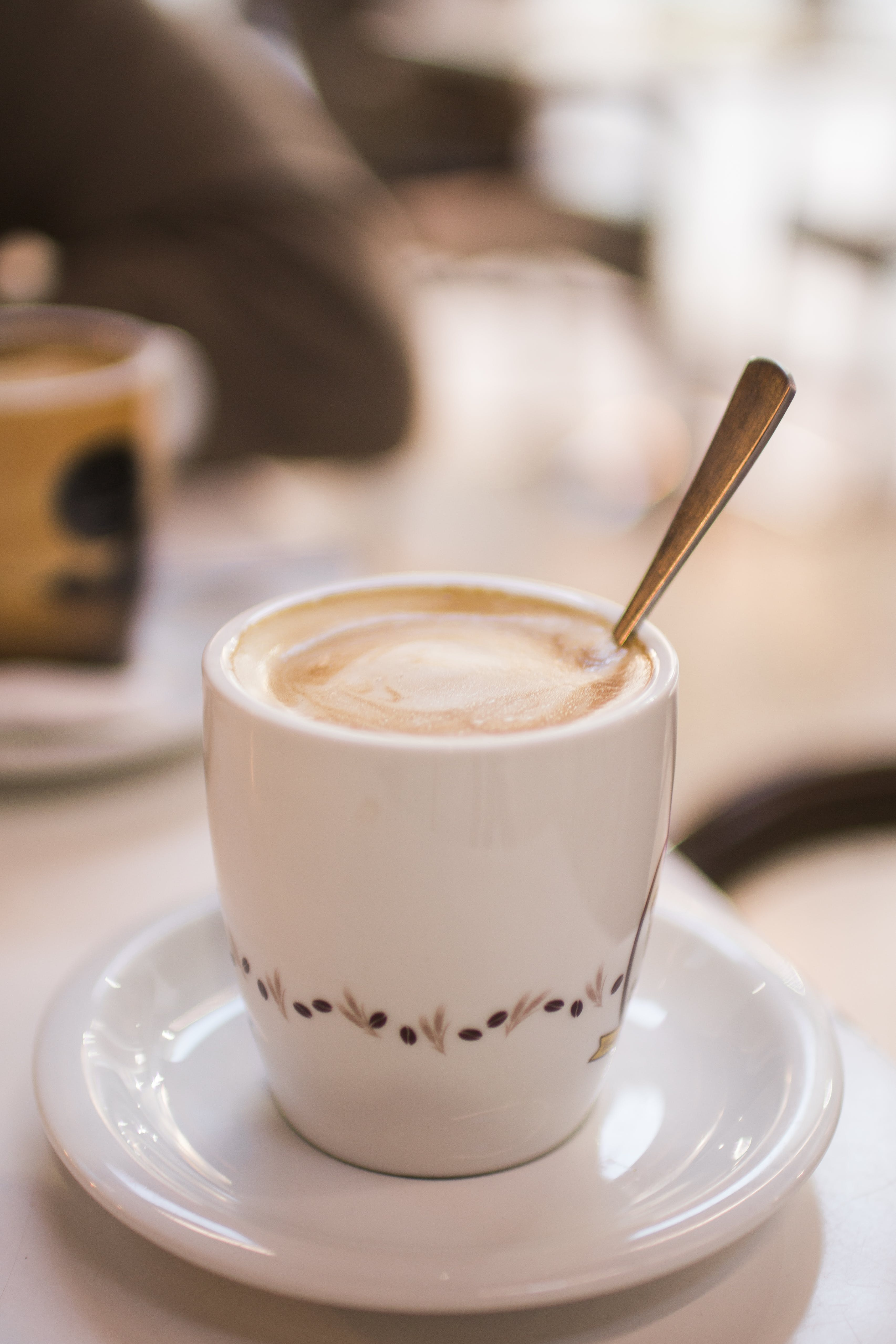 White and Brown Ceramic Cup Filled With Latte on White Ceramic Saucer