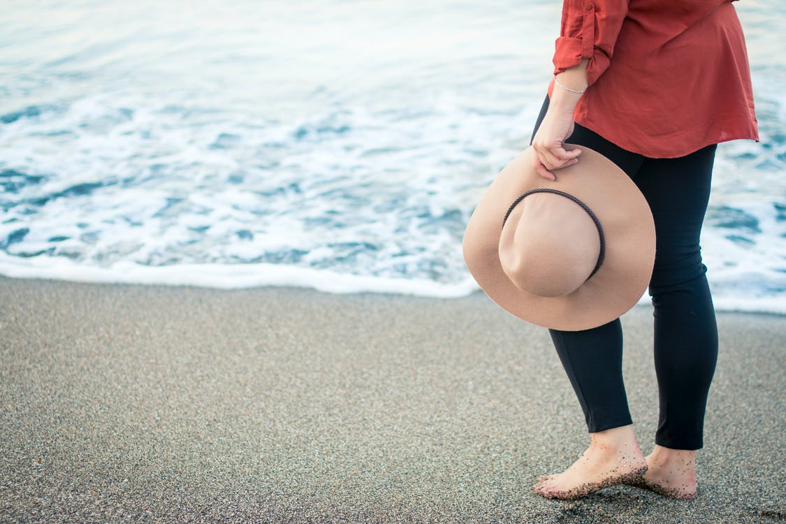 Woman Holding Brown Hat Standing on the Seashore
