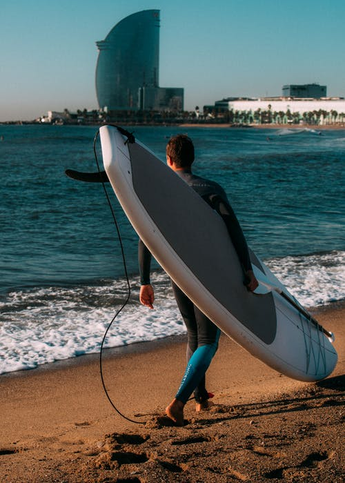 Man Carrying White Surfboard