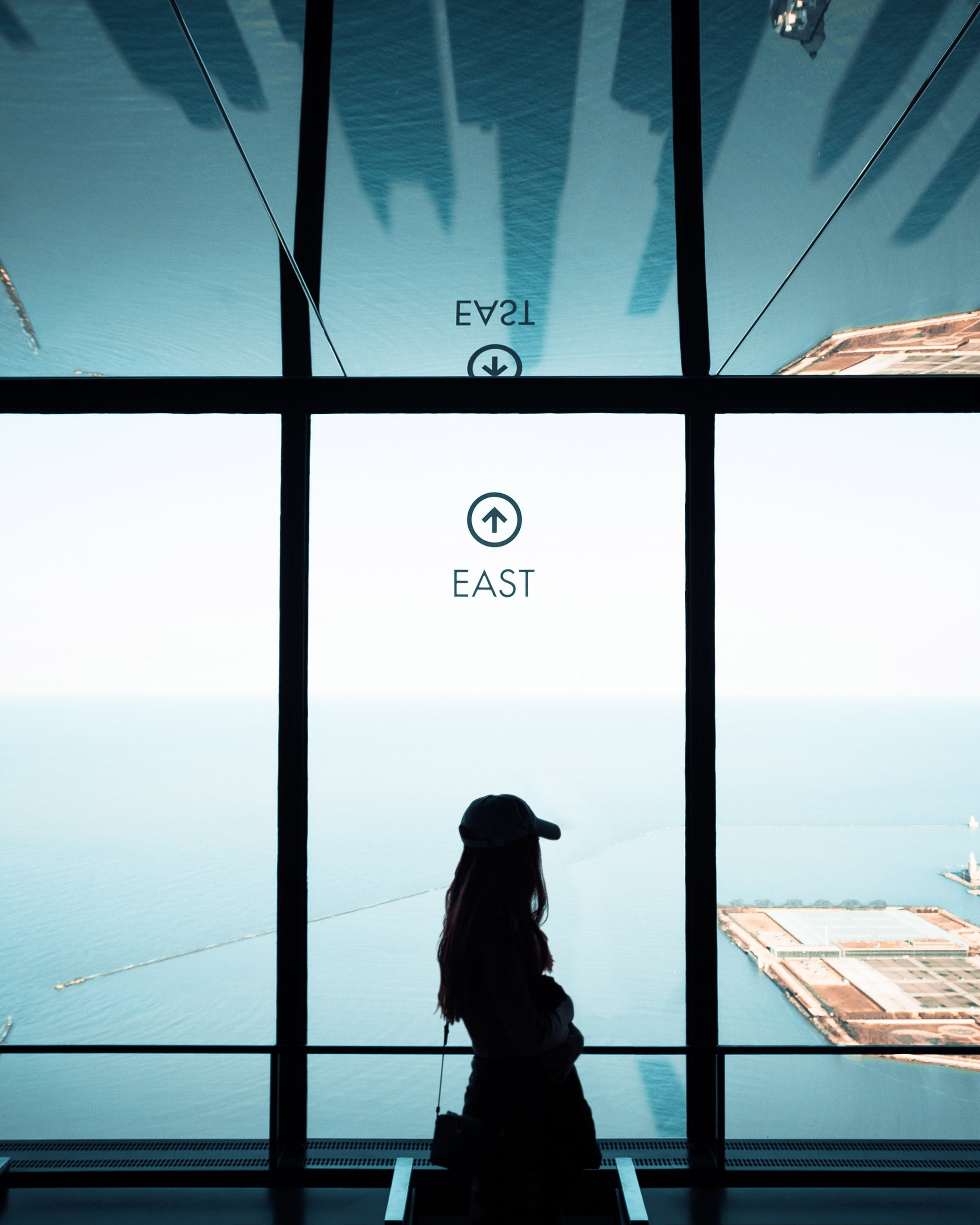 Woman Standing Near Full Glass Window