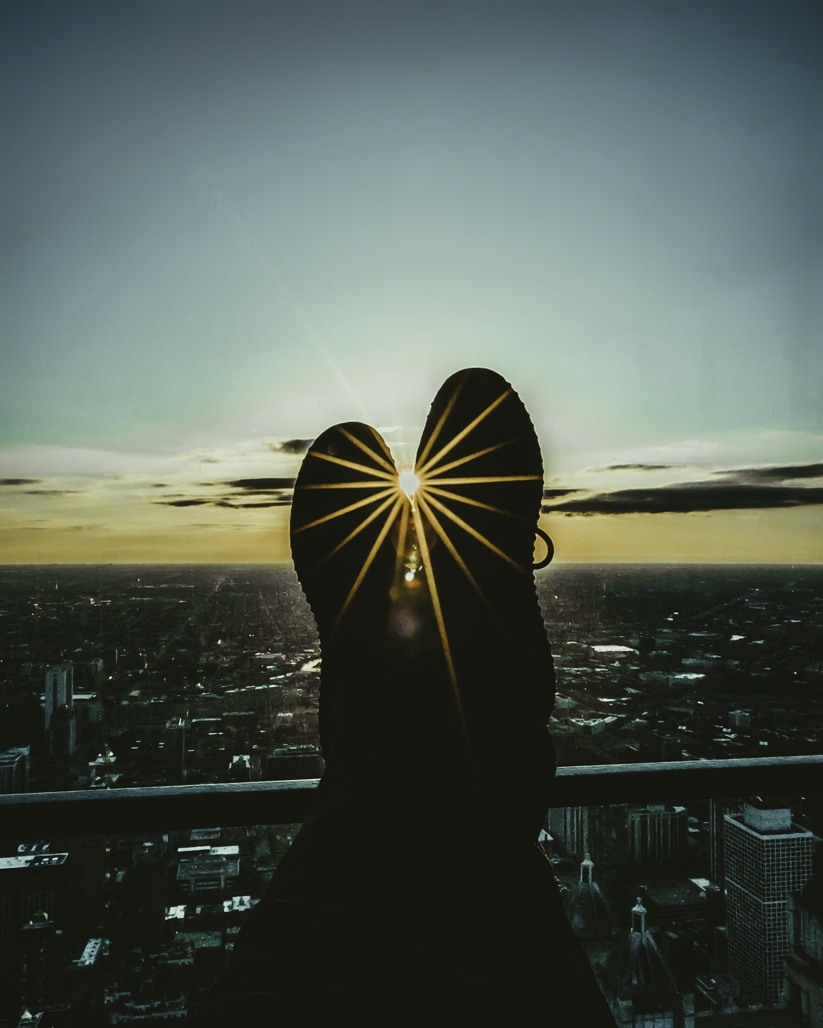 Silhouette of Person's Feet Leaning on Railings during Golden Hour