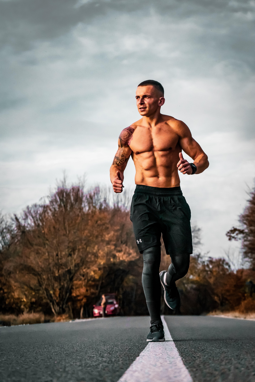 Man in Black Short Running on Pavement Road