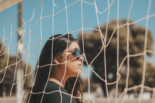Woman Wearing Black Sunglasses Standing Beside Sports Net