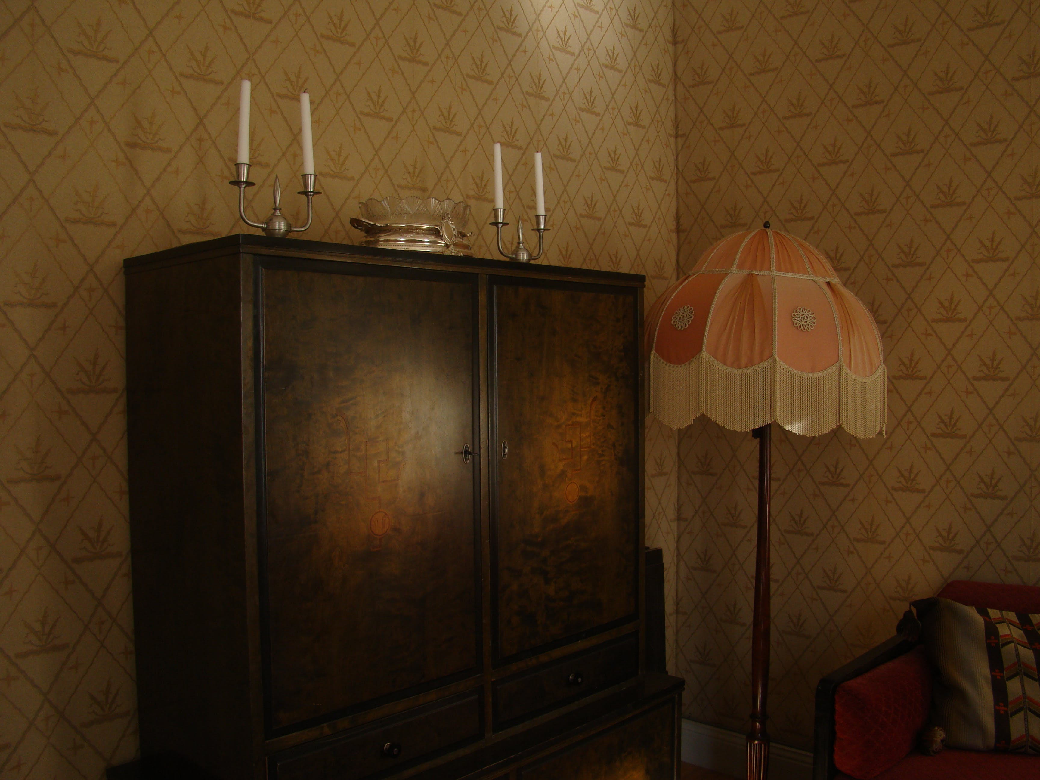 Black Wooden Wardrobe and White and Pink Pedestal Lamp Inside the Room