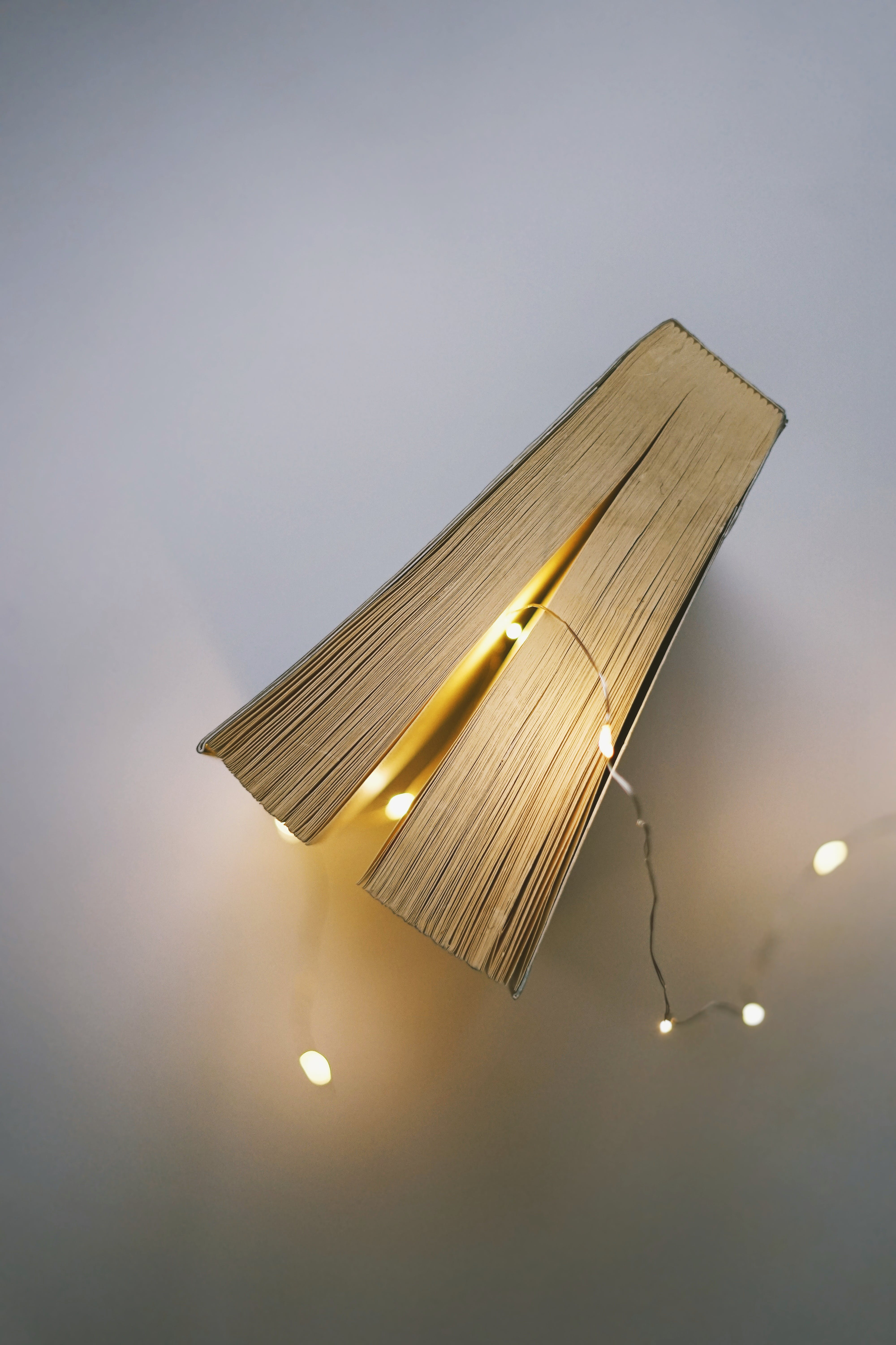 Closed Book Beside Gray String Light on White Surface