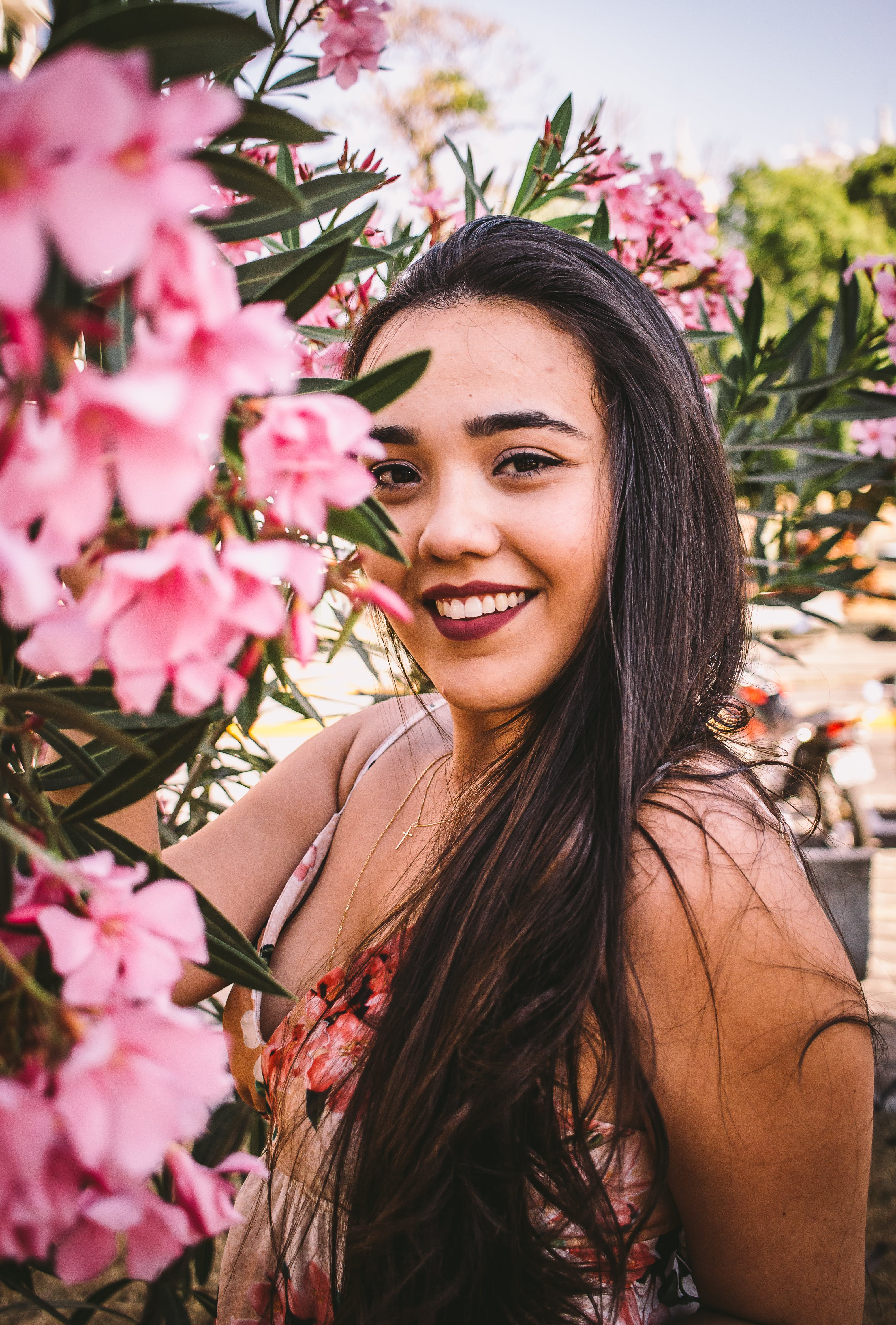 Woman Smiling Surrounded By Pink Flowers