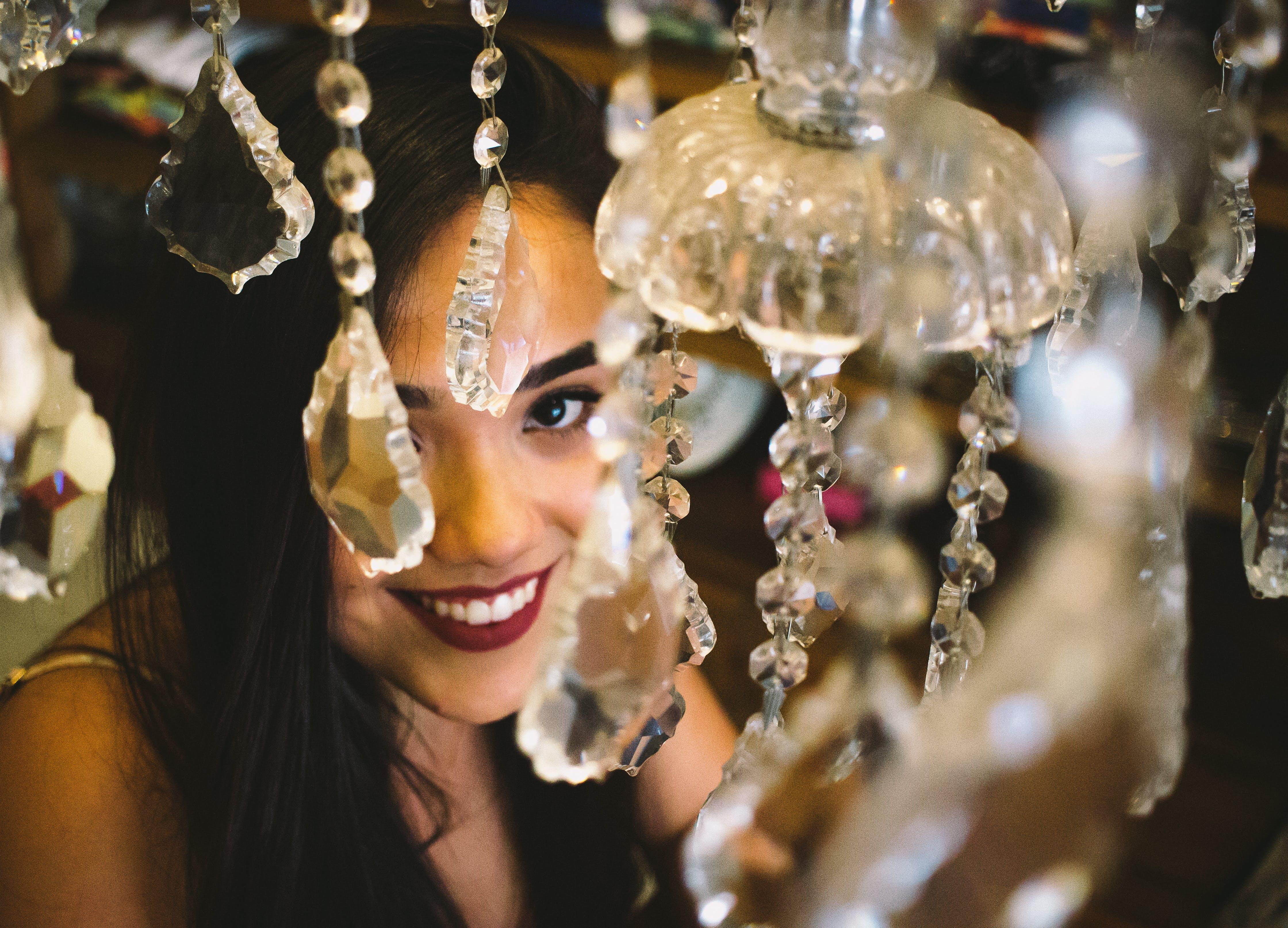 Woman Smiling Near Crystal Chandelier