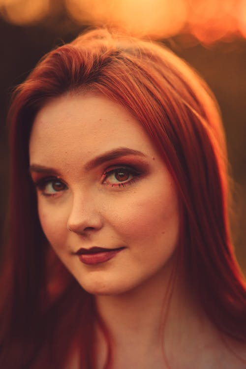 Redhead woman with bright makeup looking at camera