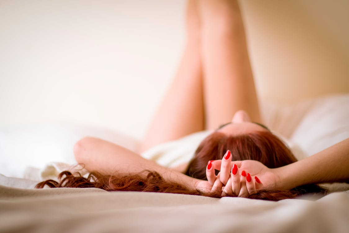 Selective Focus Photography of Woman Lying on Bed