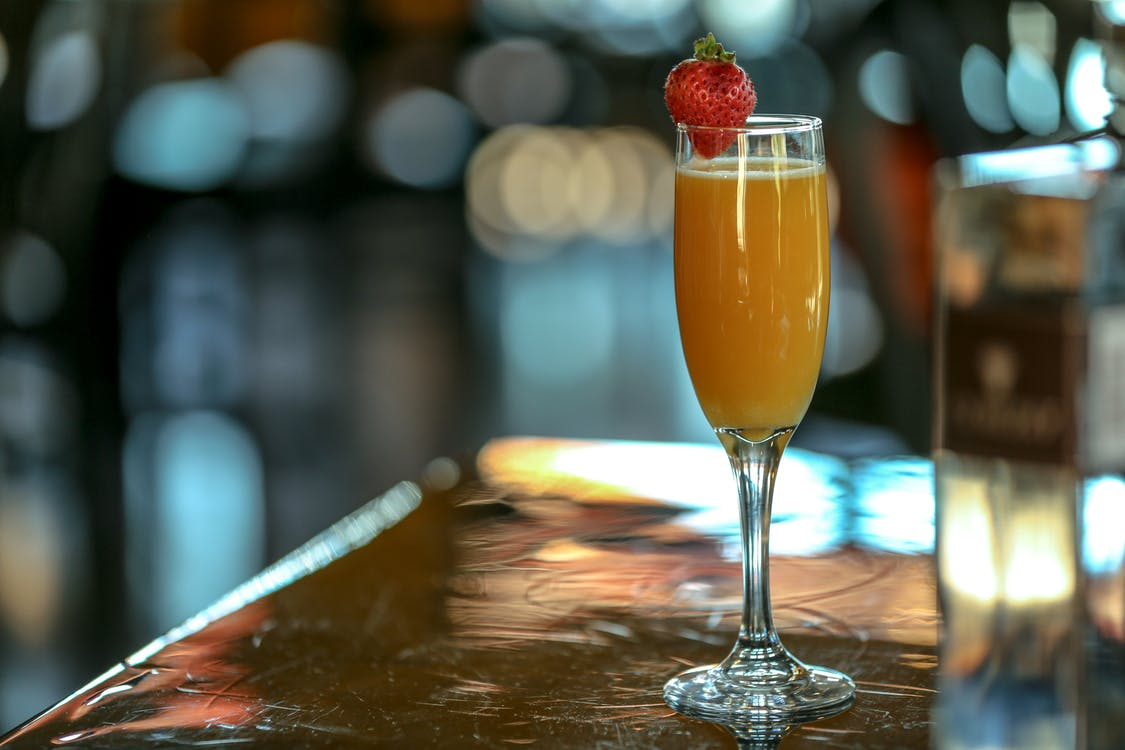 Orange Liquid Filled Champagne Flute on Brown Surface