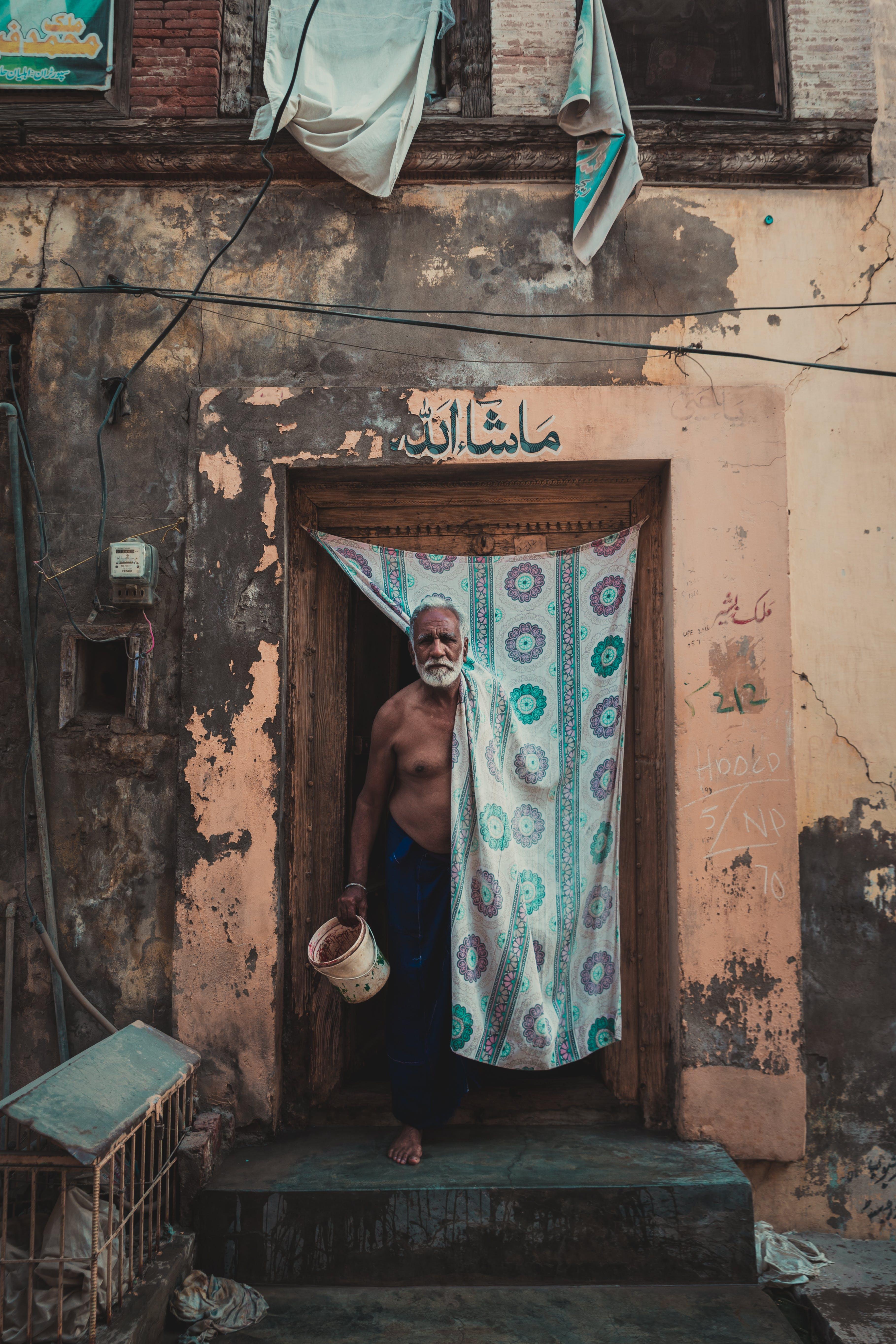 Standing Man Holding Plastic Pail Inside Building