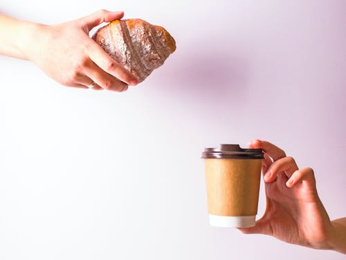 Person Hand Holding Disposable Cup and Croissant
