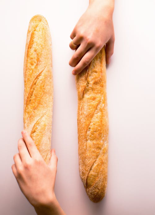 Persons Holding Bread