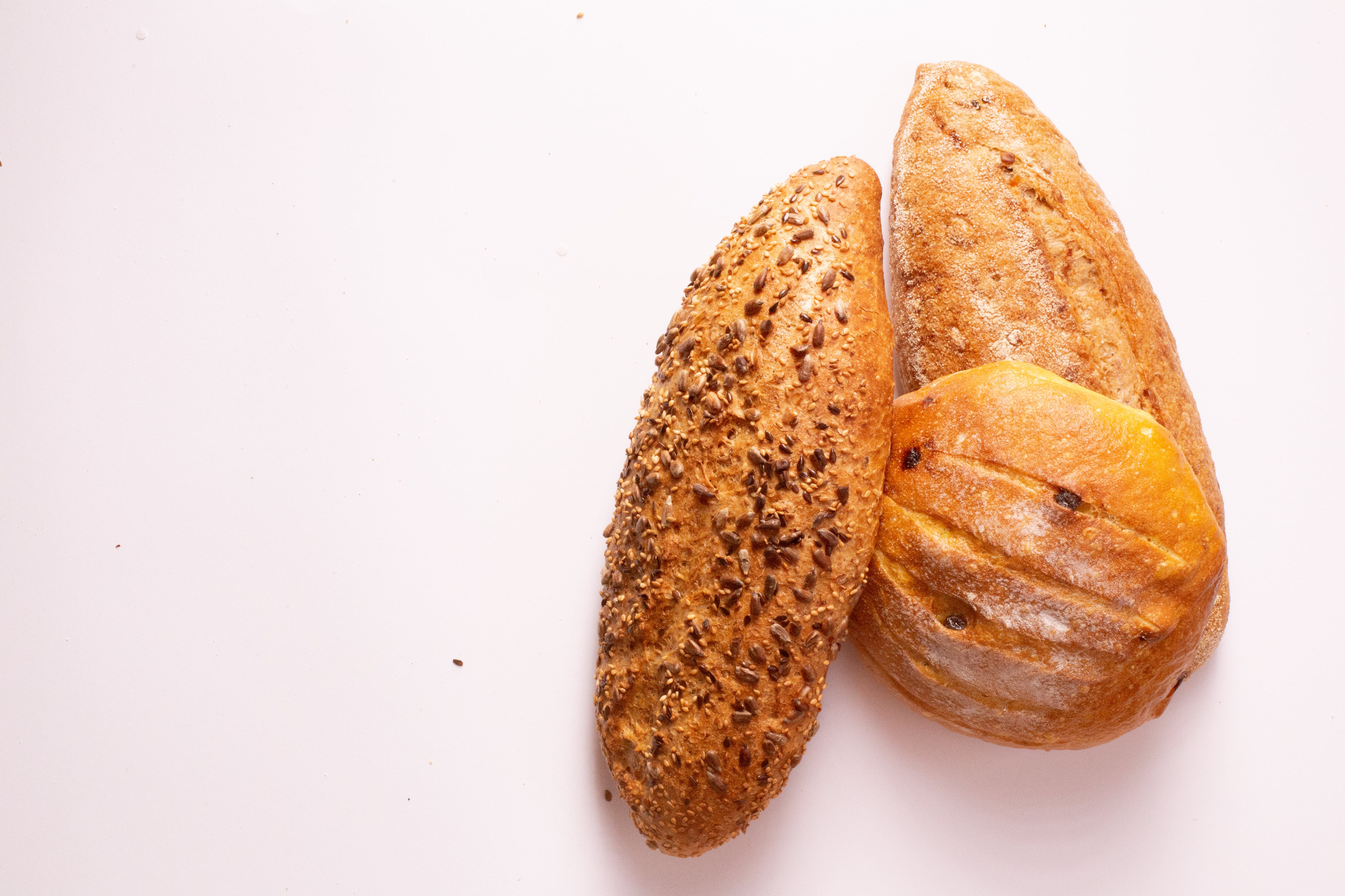 Three Breads on White Surface