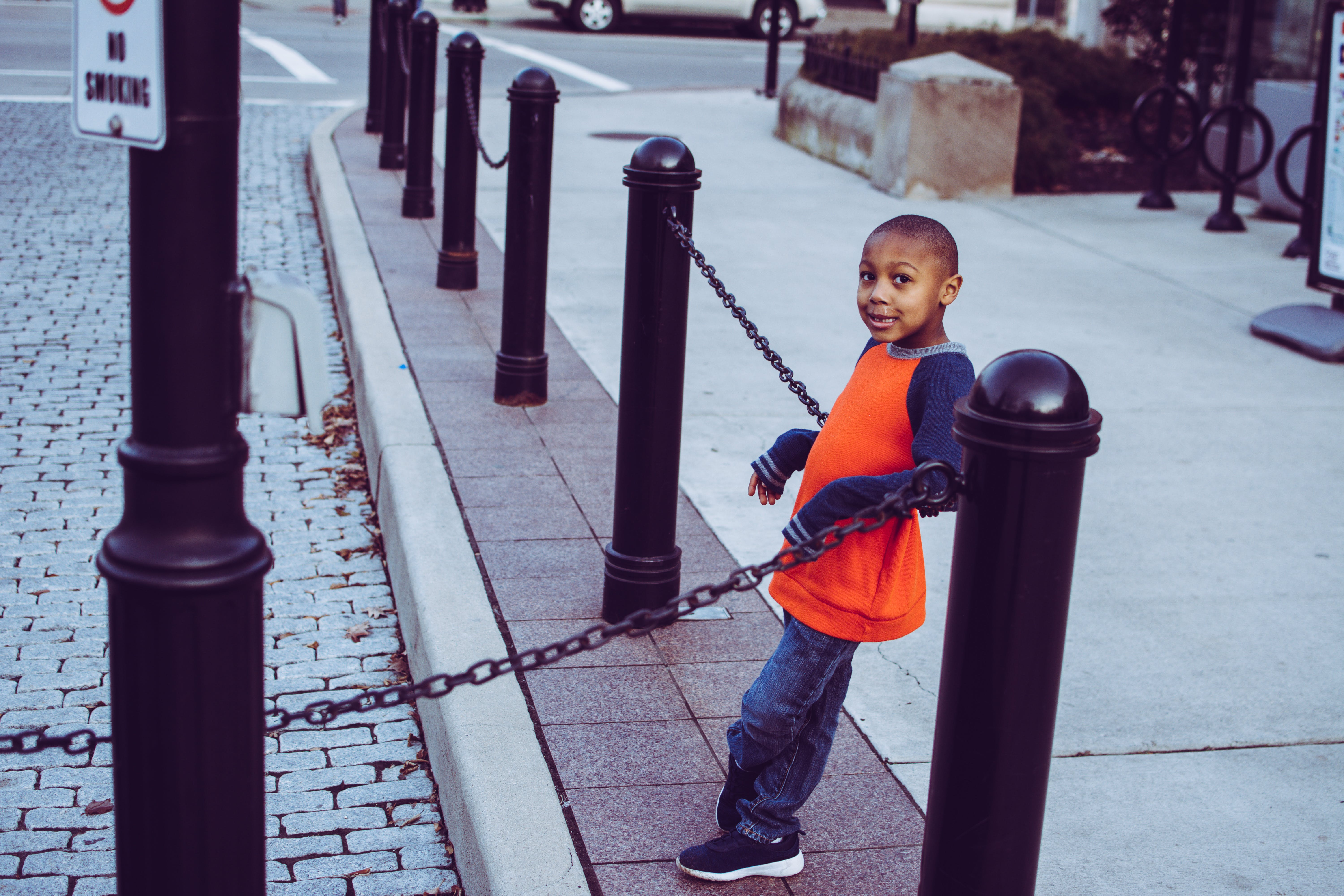 Boy Leaning On Chain Fence