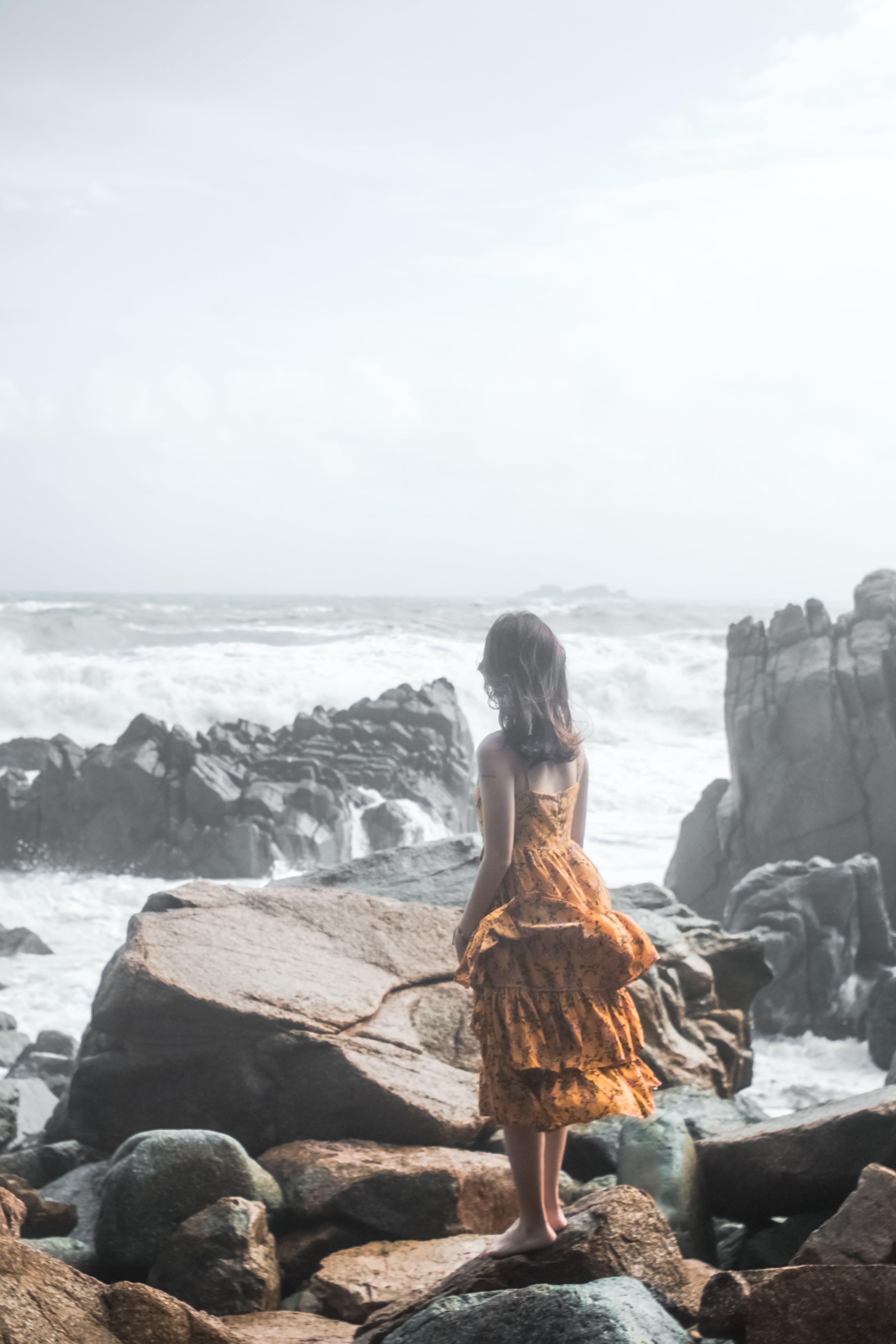 Woman in Orange Dress Standing on Rock Groynes