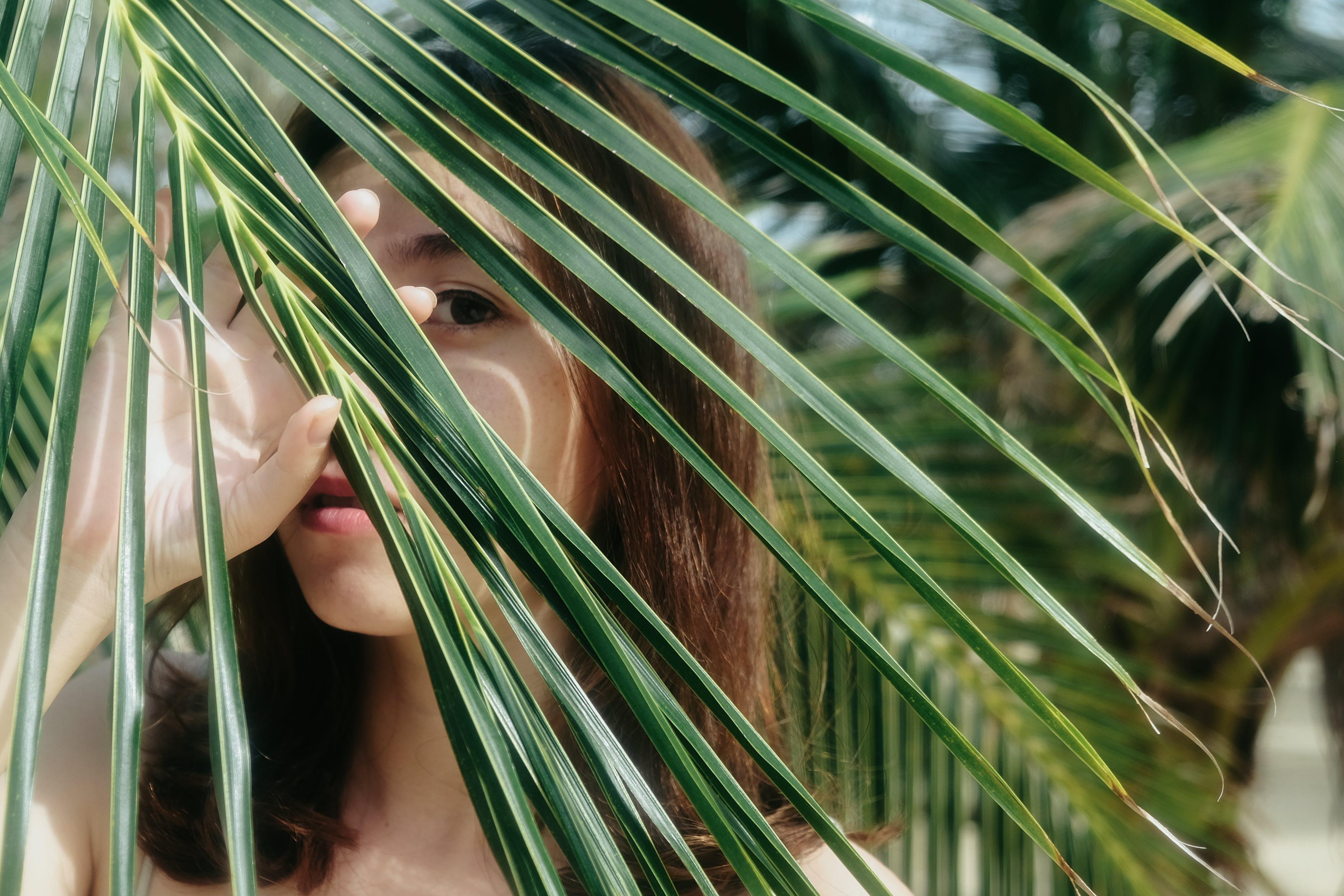 Woman Taking Selfie Behind Palm Leaf