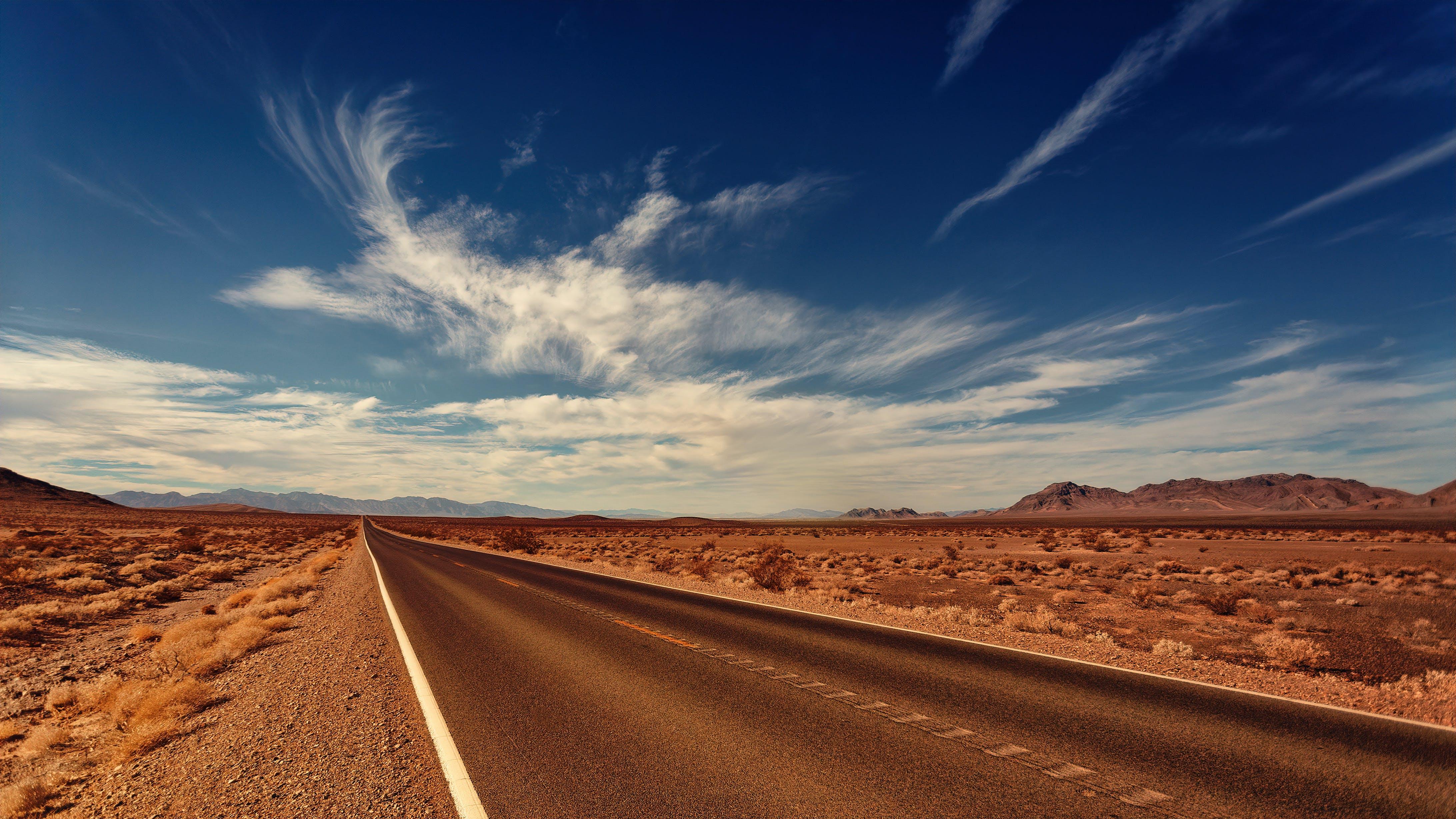 Asphalt Road Under White Clouds