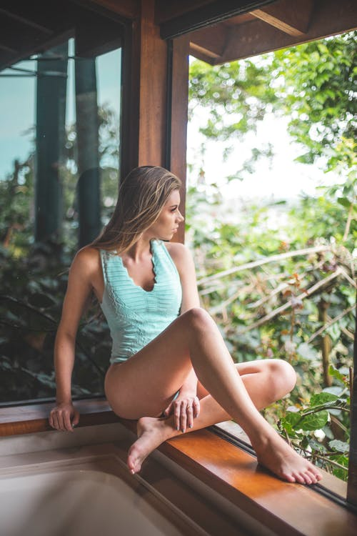 Woman In Teal Swimsuit Sitting By The Window