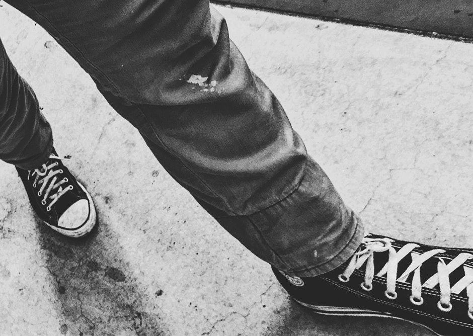 Person Walking Wearing Black Shoes in Grayscale Photography