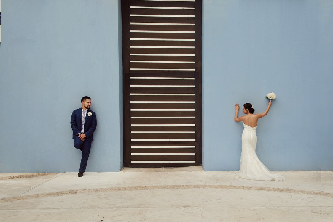 Newlyweds Leaning On Blue Wall