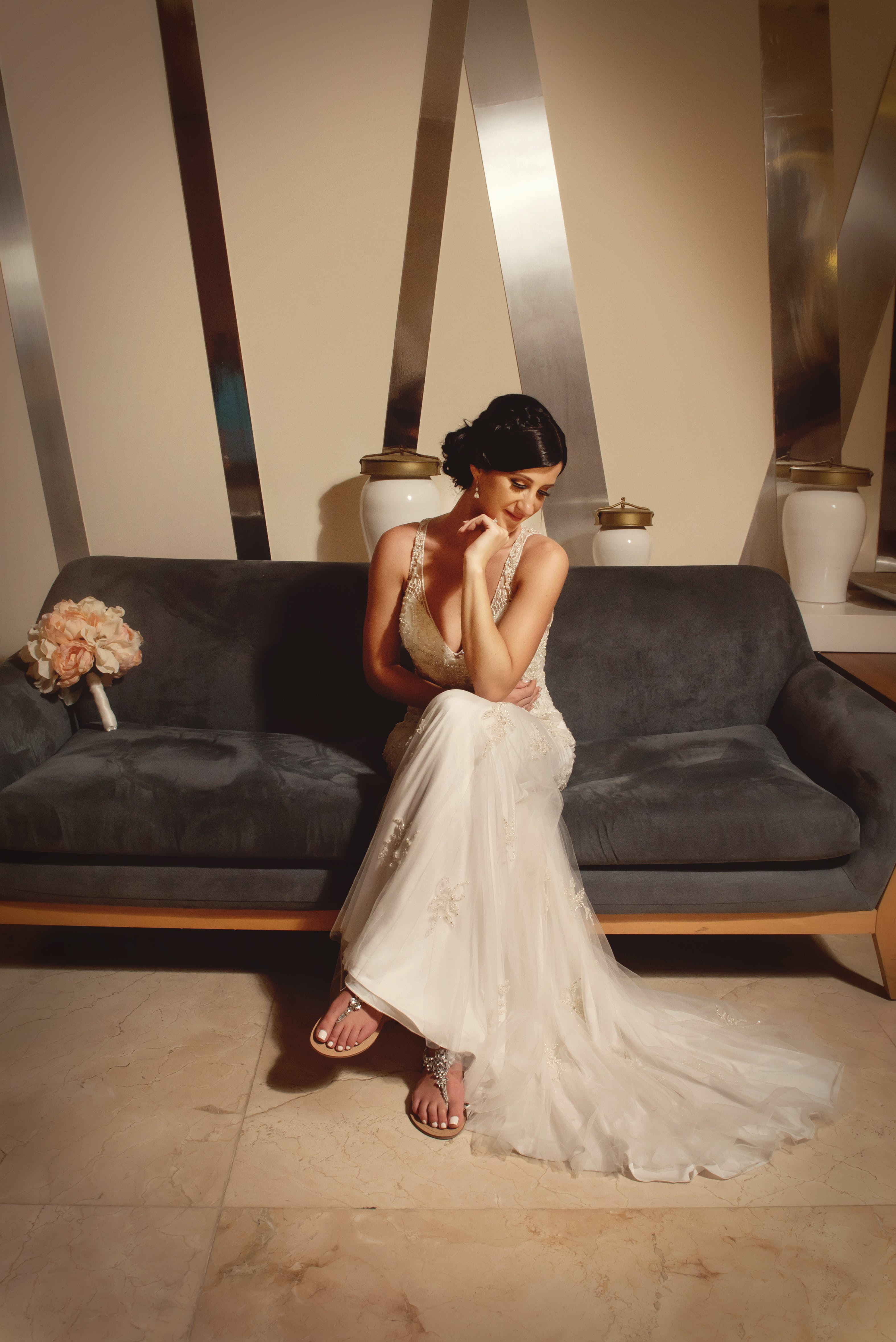 Woman In Wedding Gown Sitting On Sofa