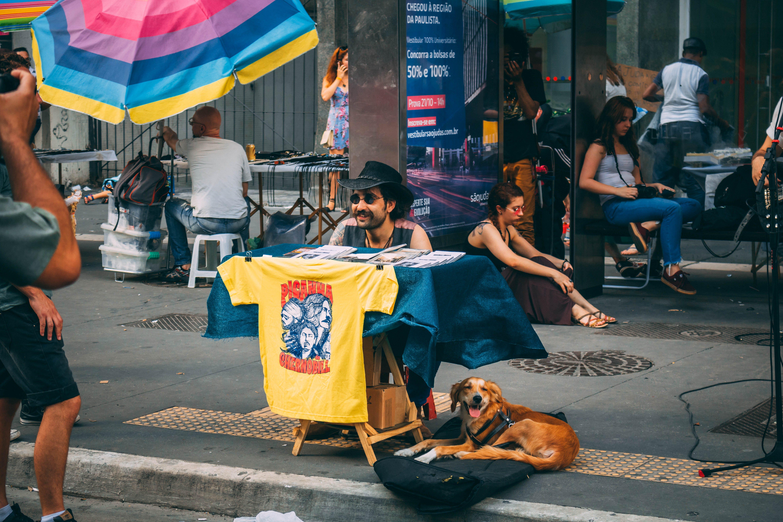 Dog Laying On Pavement Beside Man Sitting