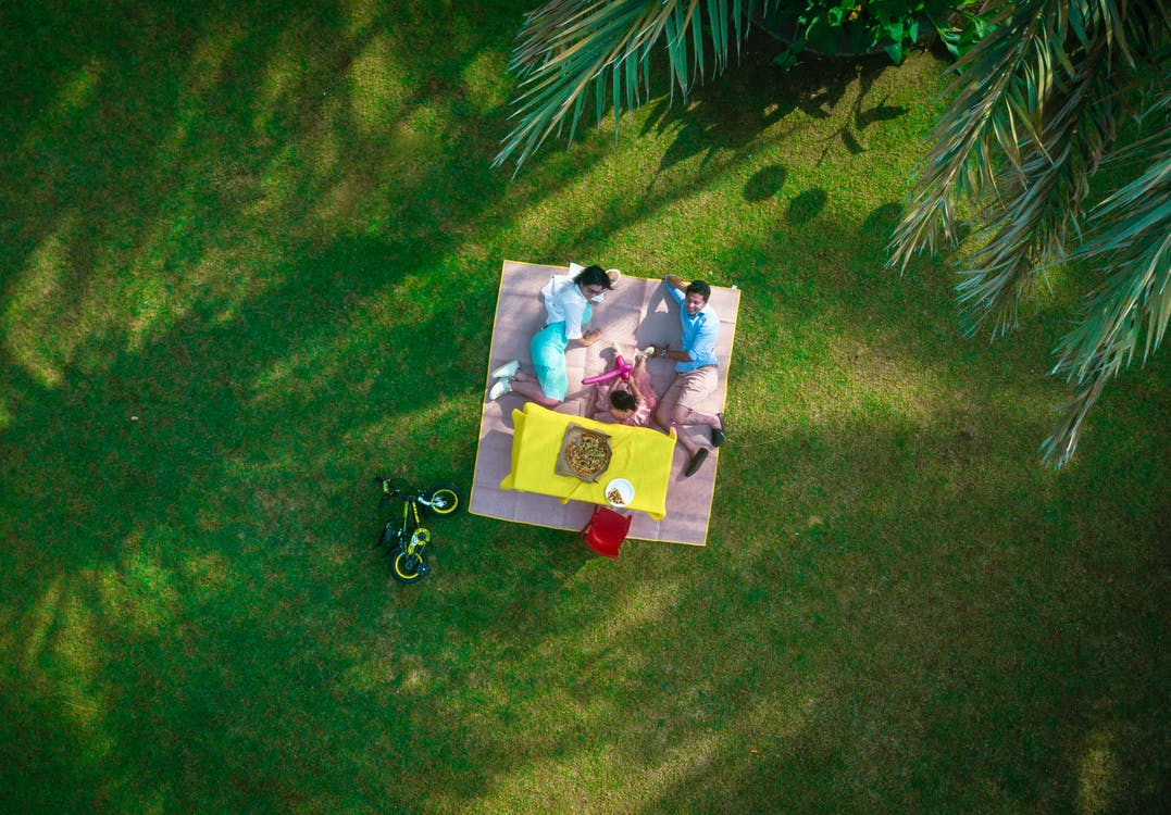 Man And Woman Laying On Picnic Mat