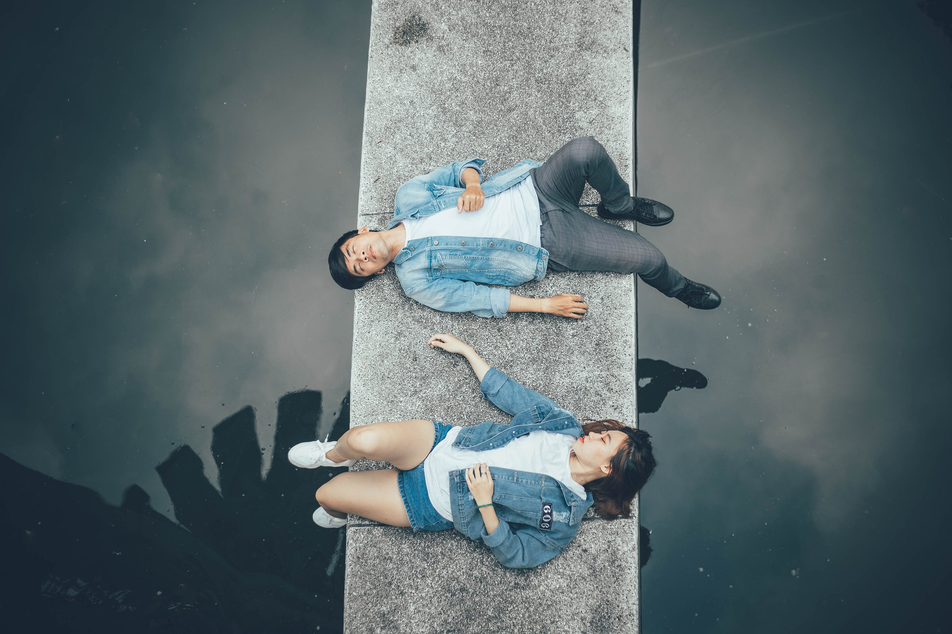 Woman and Man Lying on Walkway
