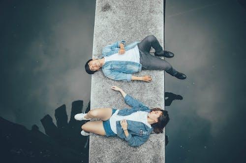 Woman and Man Lying on Walkway