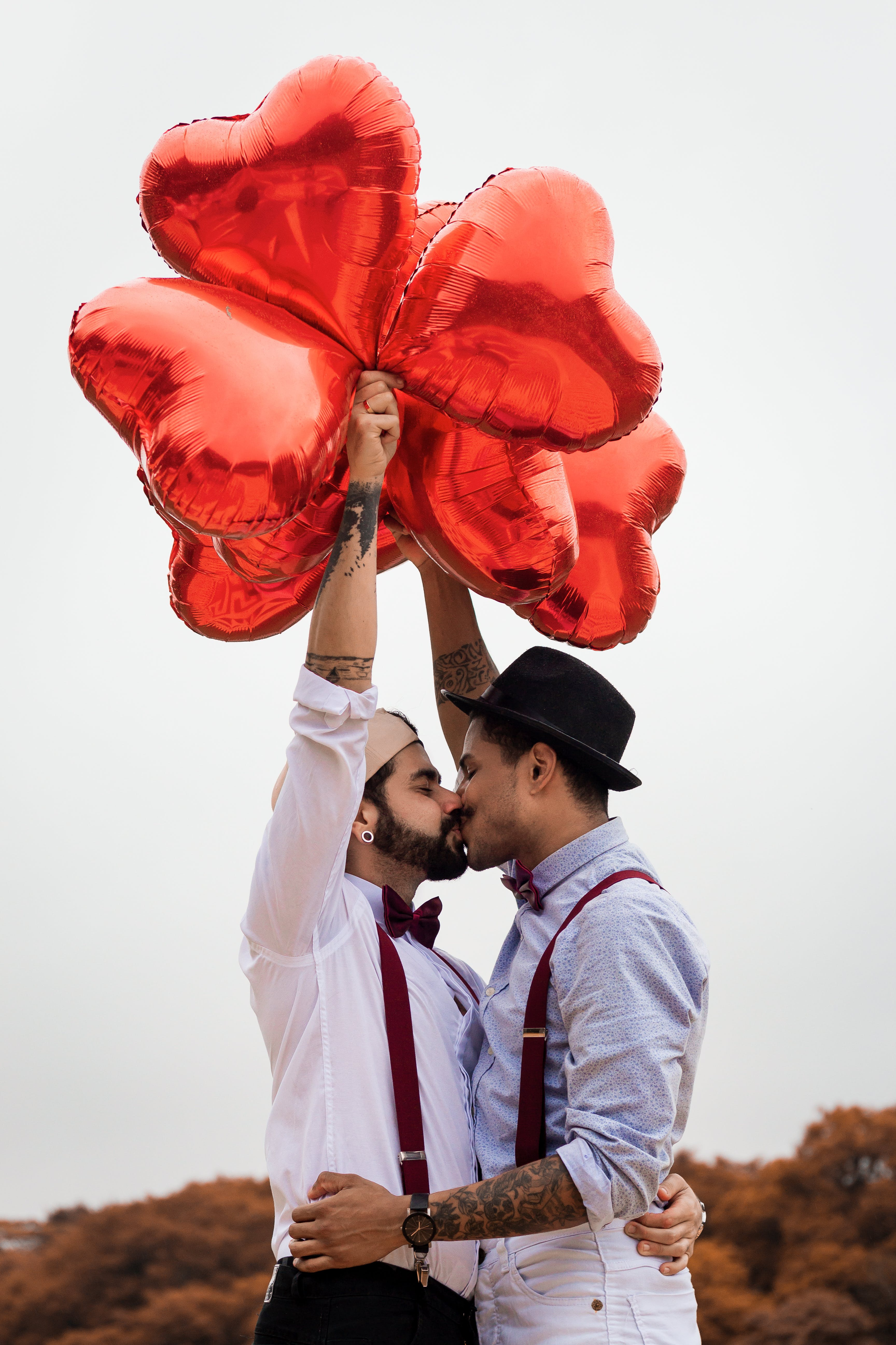 Two Men Kissing And Holding Balloons