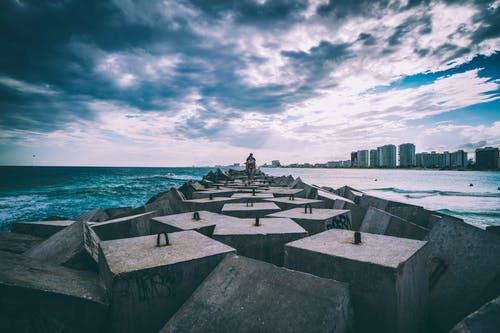 Concrete Slabs on Body of Water Under Cloudy Sky