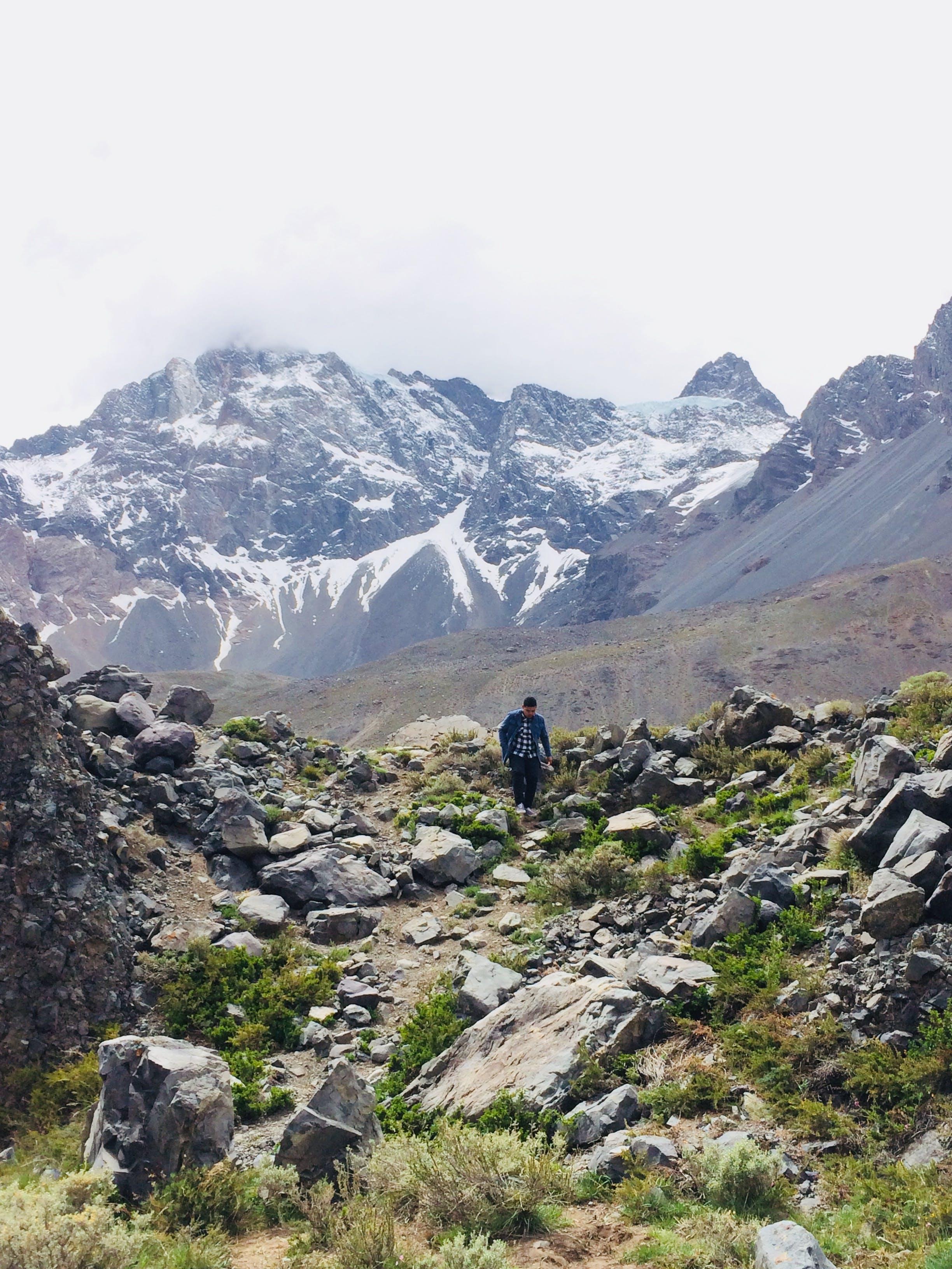 Man Walking on Rock Background of Mountain