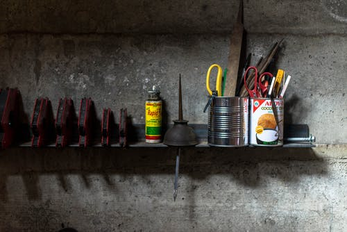 Assorted-color Scissors and Pens in Tin Cans on Brown Wooden Wall Shelf