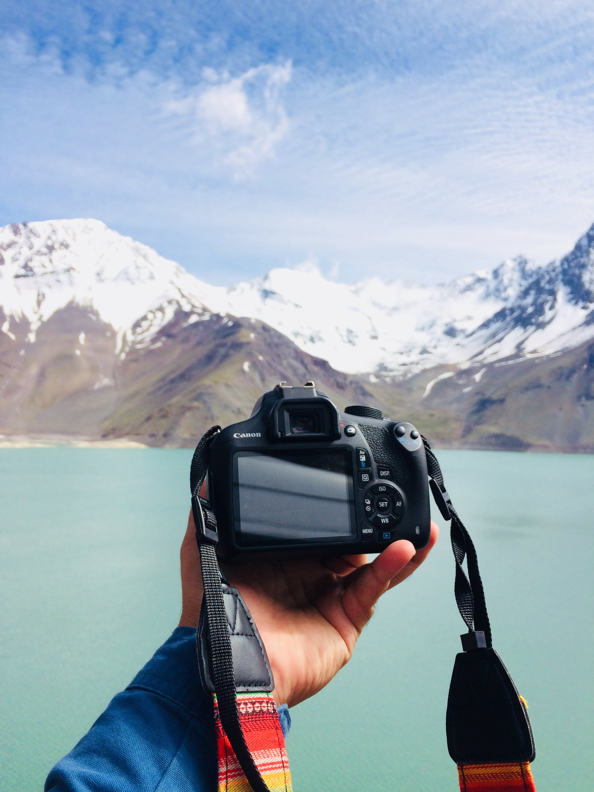 Person Holding Black Canon Dslr Camera in Front Body of Water
