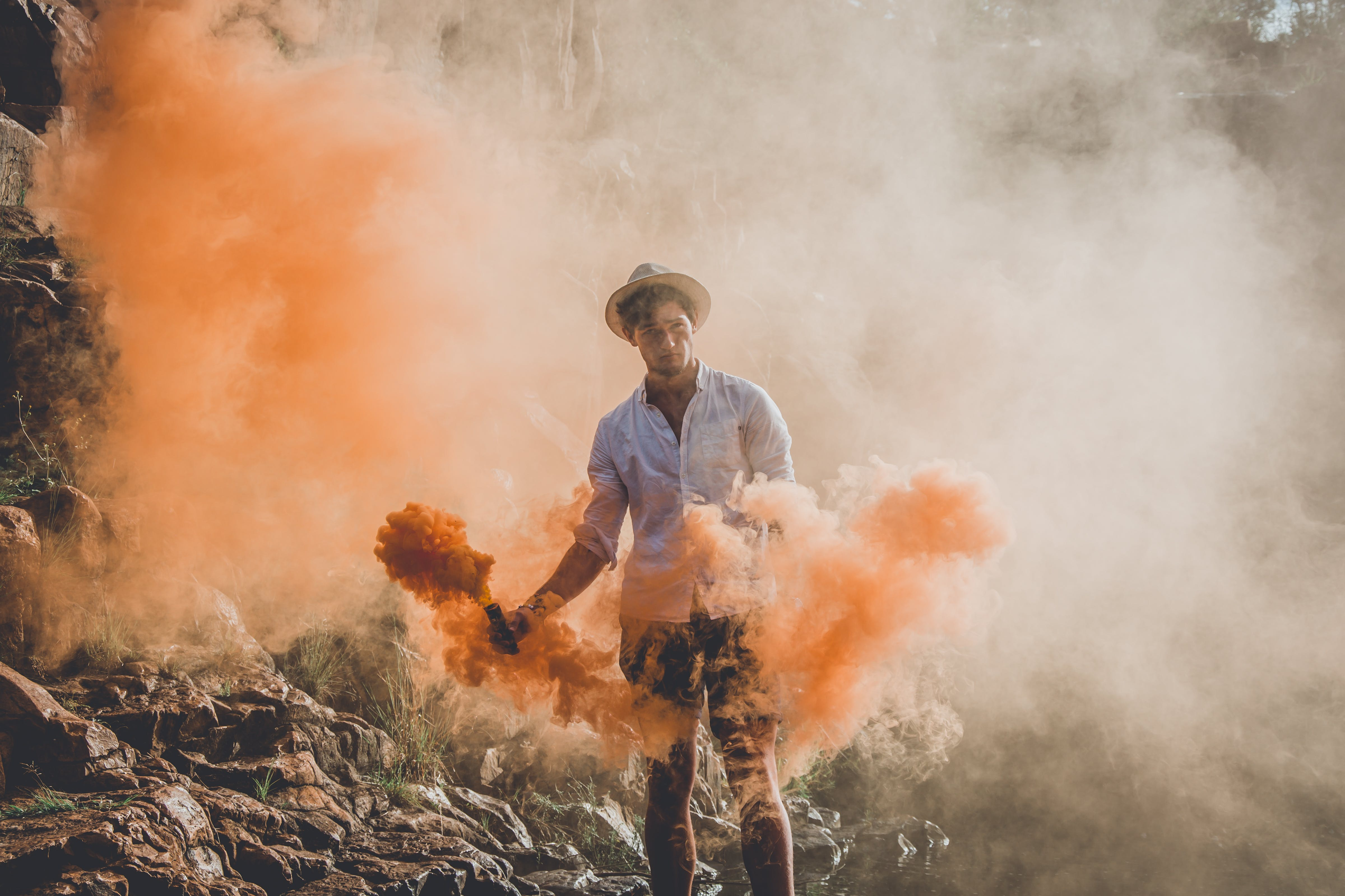 Man Standing While Holding Smoke Grenades
