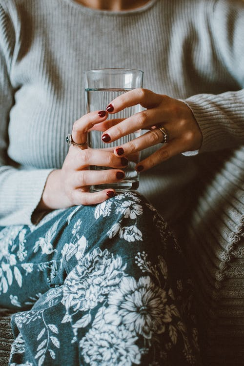 Person Sitting on Grey Sofa While Holding Clear Highball Glass of Water