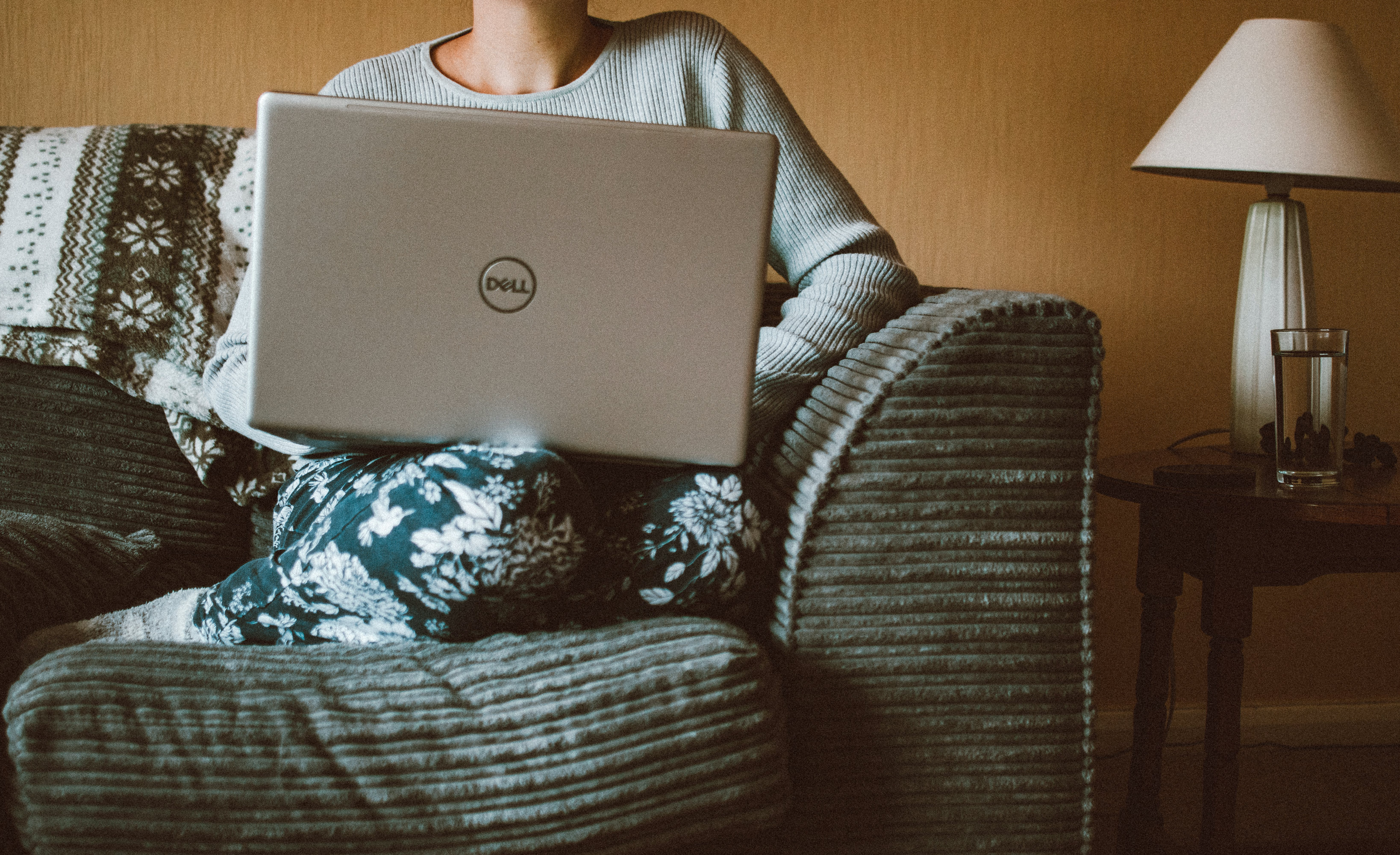 Person Using Dell Laptop While Sitting On Sofa Inside Room