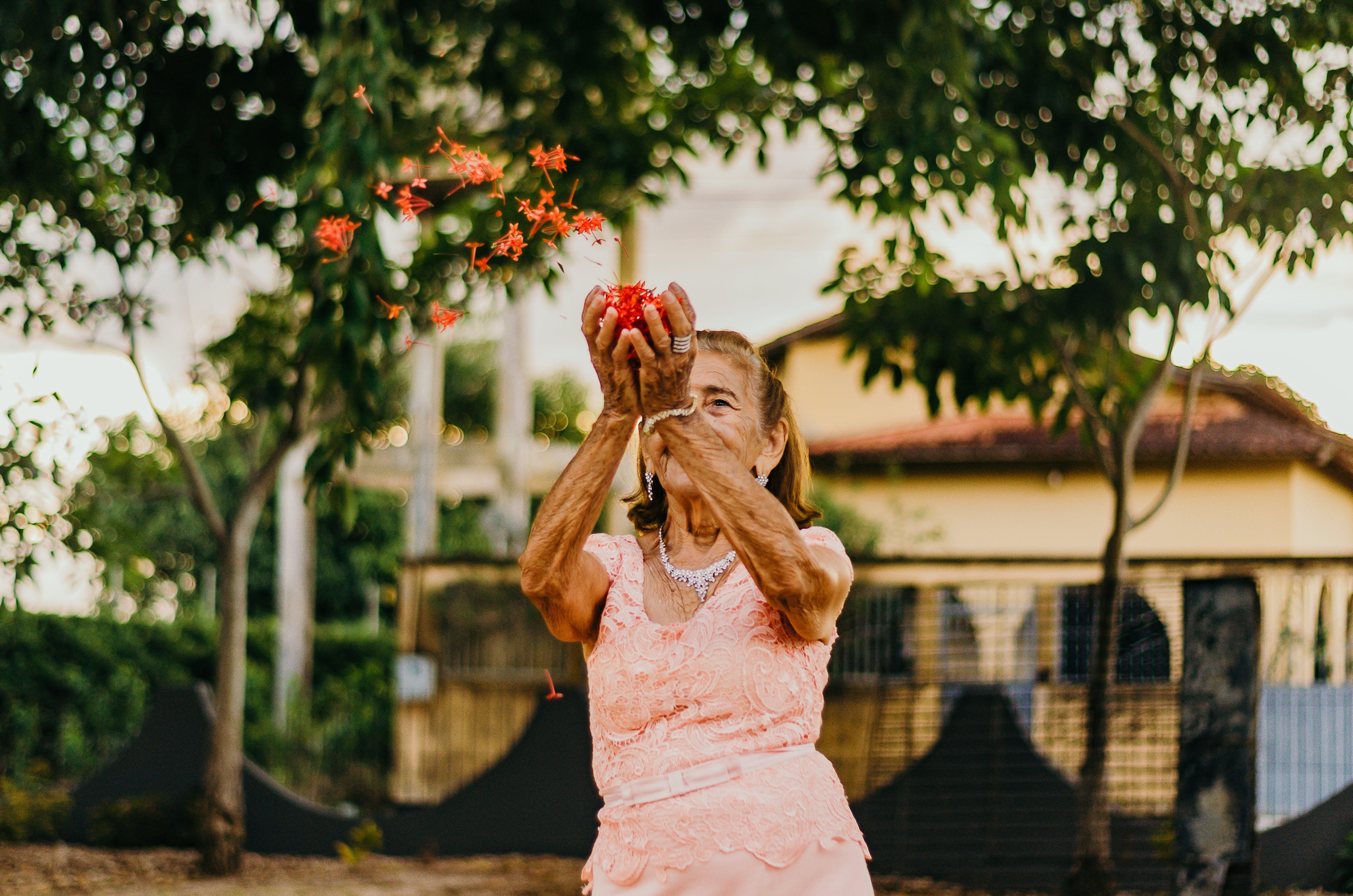 Woman in Pink Dress Throwing Flowers
