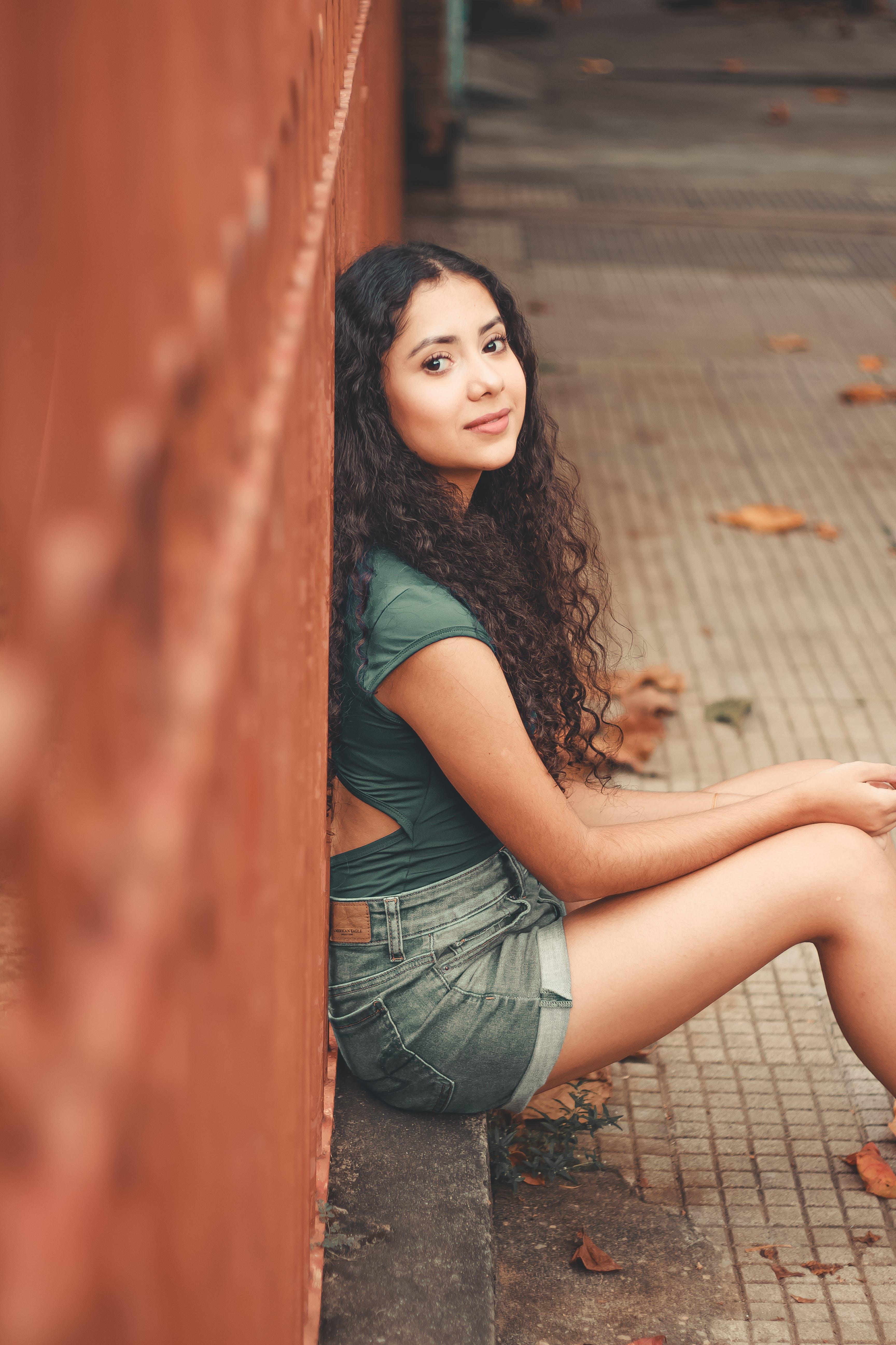 Photo of Woman Sitting Beside Wall