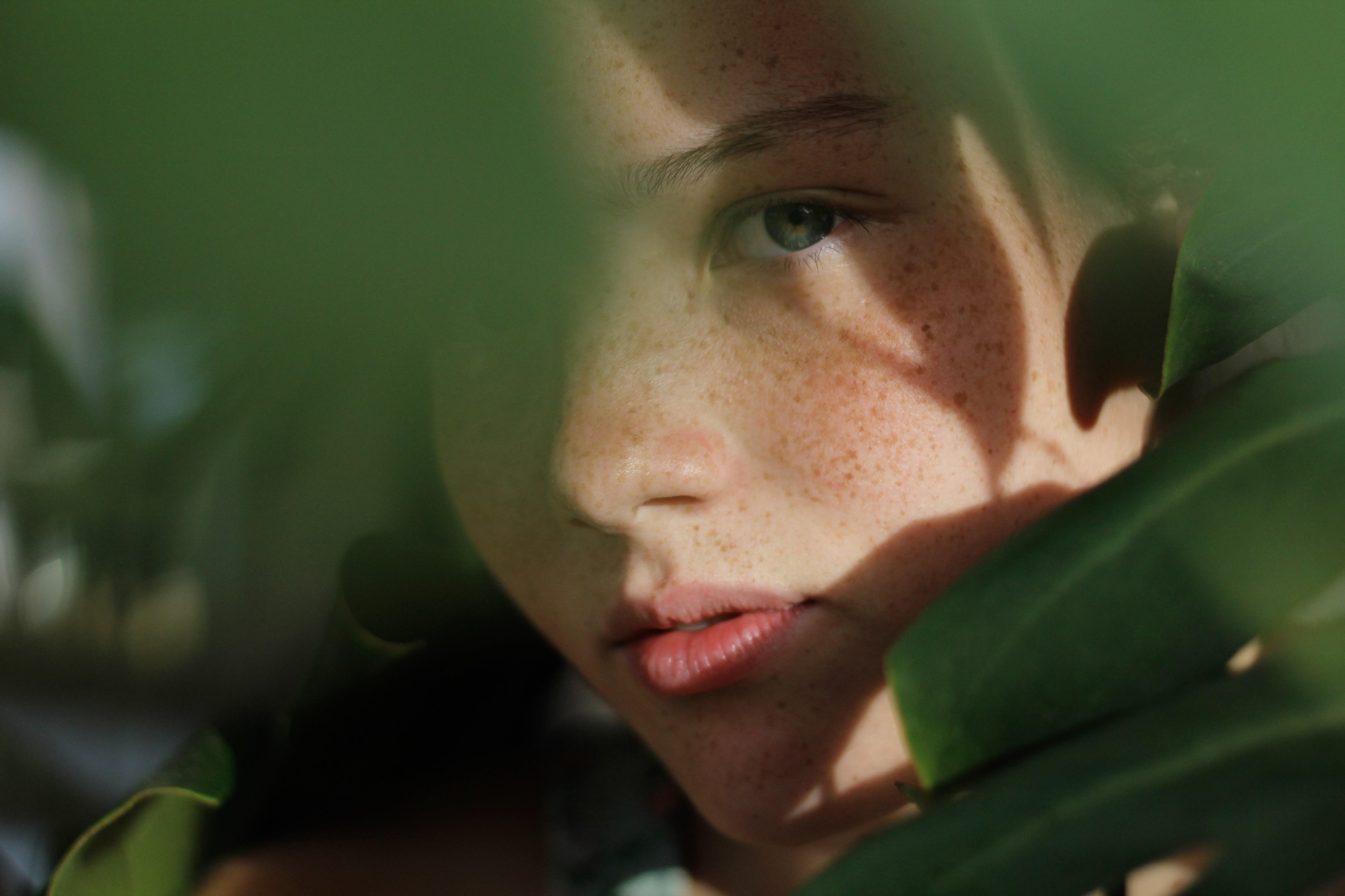 Close-up Photo of Woman Hiding Behind Green Leaves