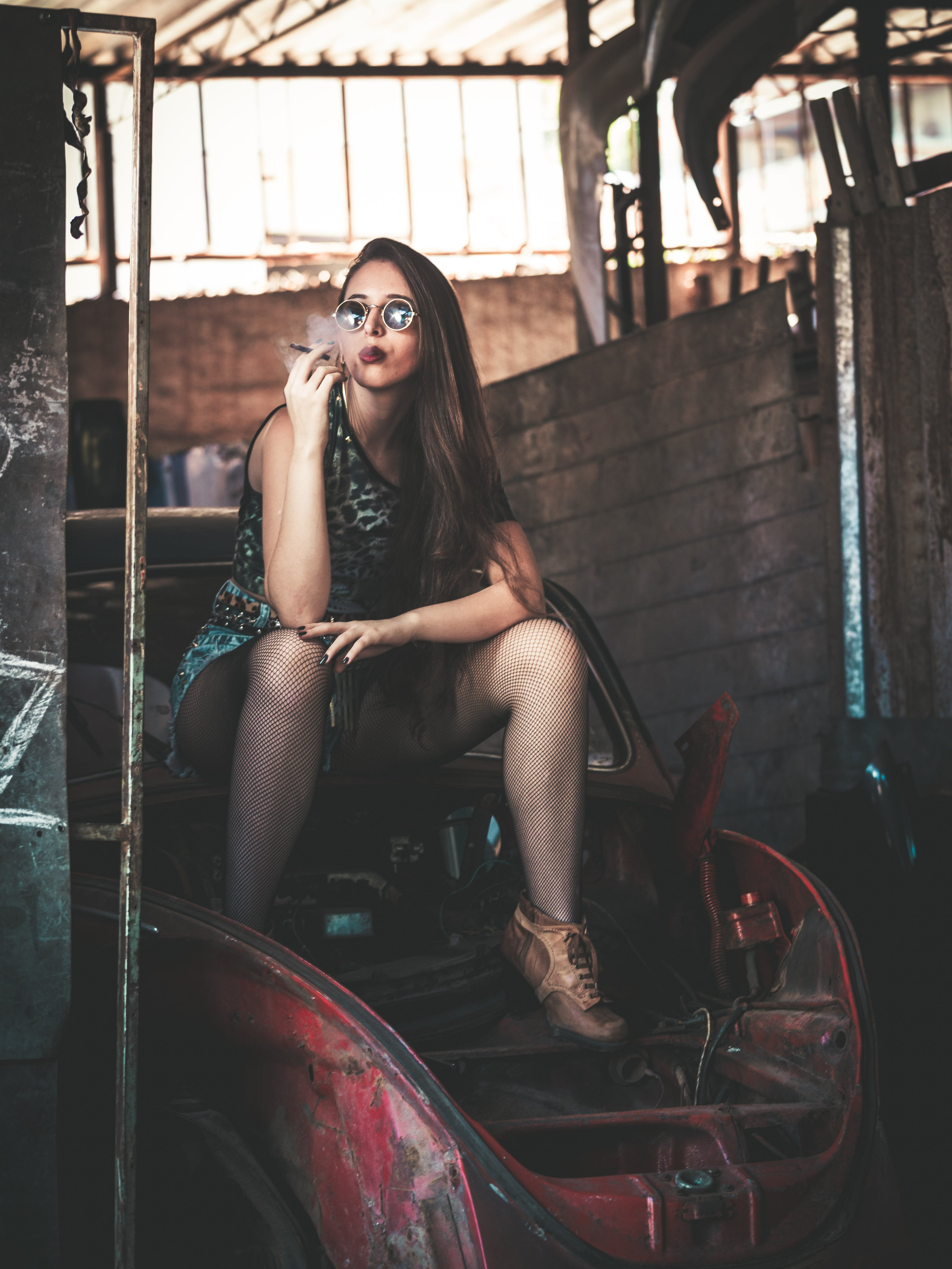 Photo of Woman Sitting on an Abandoned Car Smoking a Cigarette