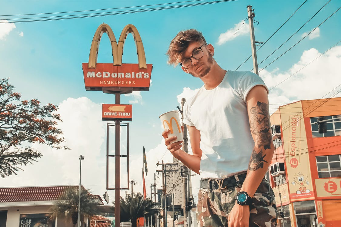 Photo of Man Holding a McDonald's Paper Cup