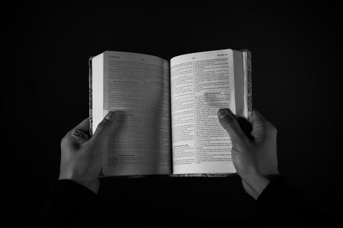 Monochrome Photo of Person Holding Book