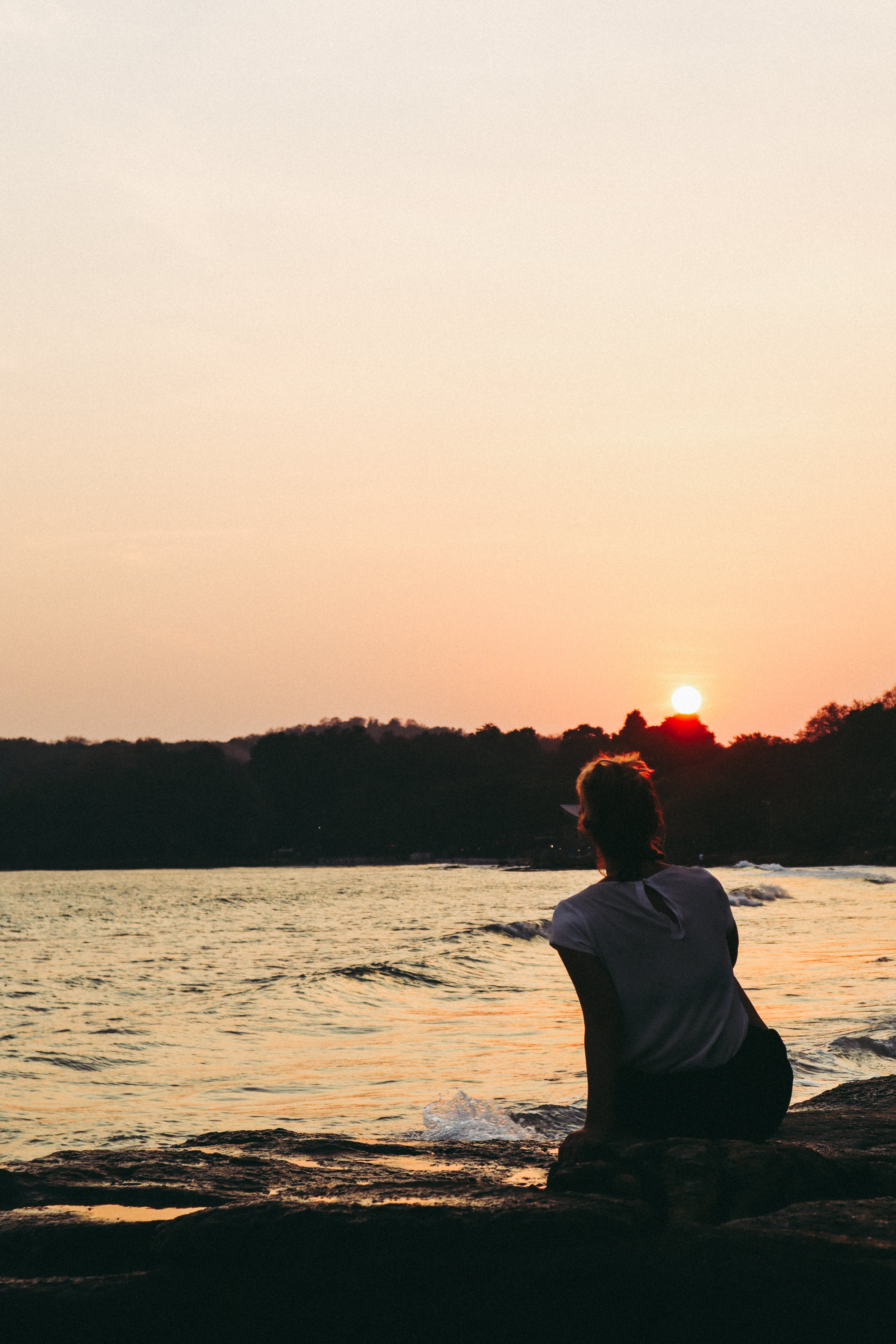 Woman Seated on a Rock Watching the Sunset
