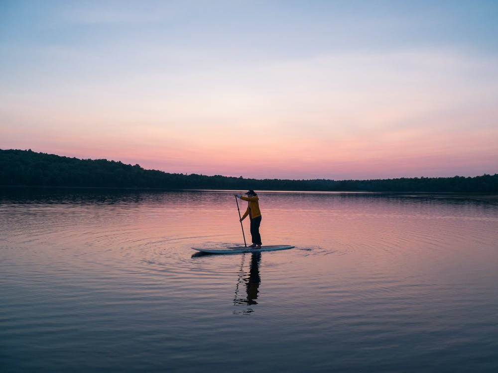 Man Riding Board on Middle of Body of Water